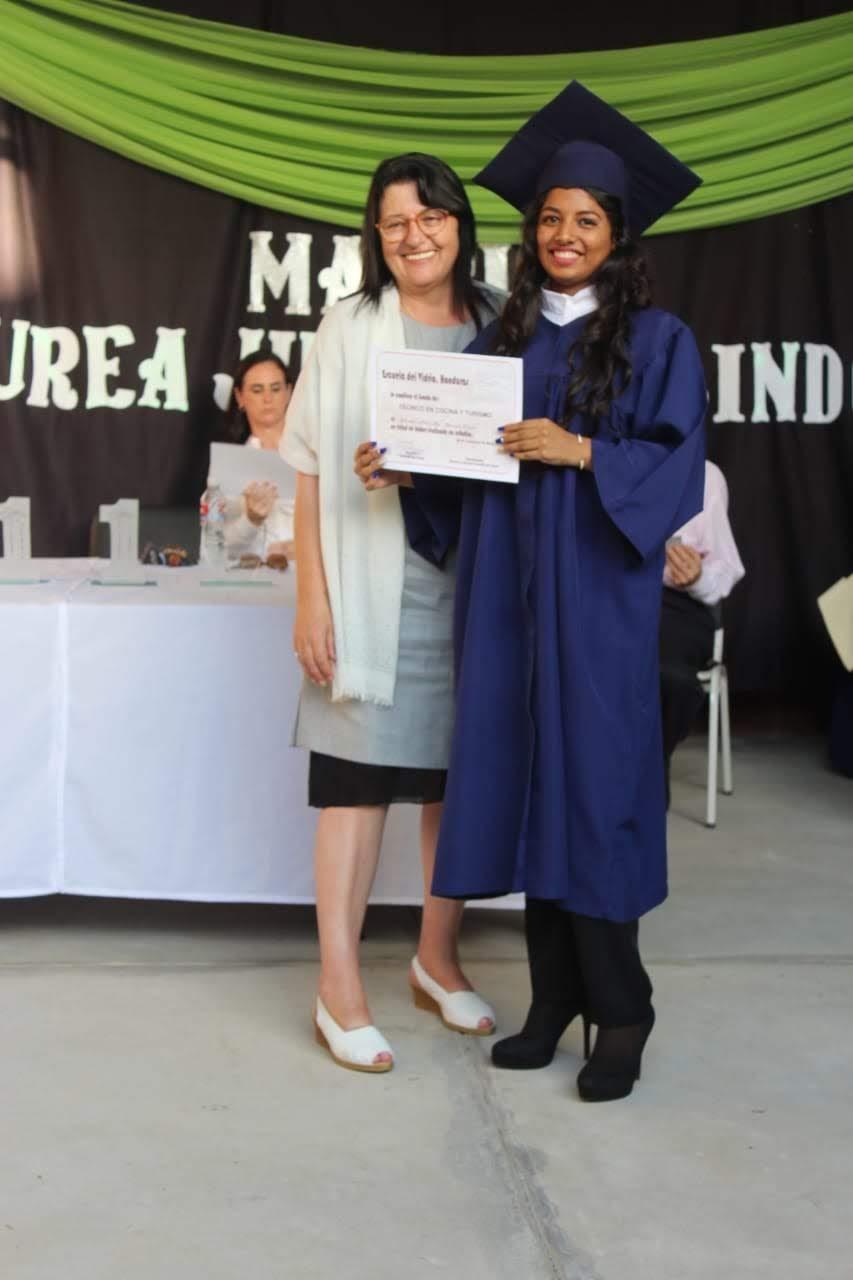 Áurea entregando el diploma de graduación a una alumna